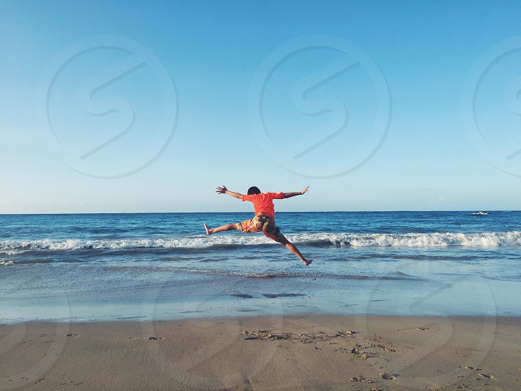 Fun family beachCaribbean boy sunny day jumping ocean vacations colors bright  photo