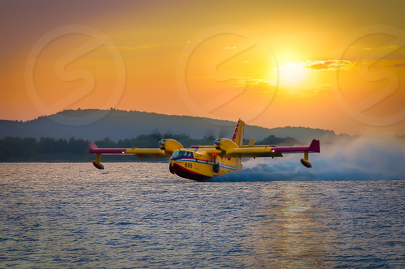 Canadair waterbomber scooping water in sunset photo
