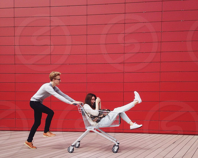 man with brown short hair pushing shopping cart while woman riding in it photo