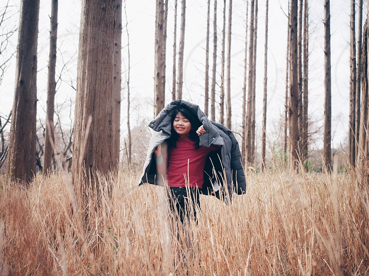 girl with grey bubble jacket walking on grassy field with trees photo
