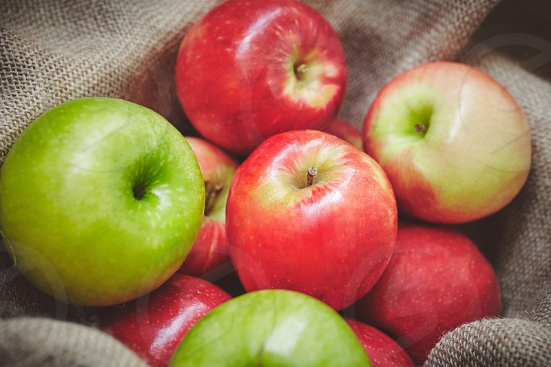 Close-up organic apples in basket cover with sackcloth on background texture Fresh apples with copy space photo