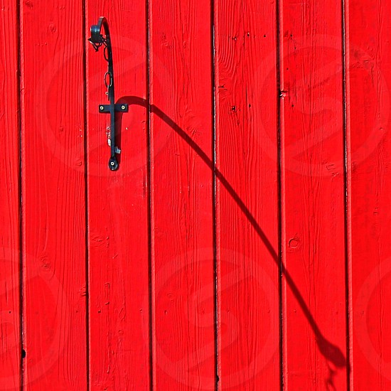 A curved hook on bright red wooden house throws its shadow shadow across the vertical boards. photo