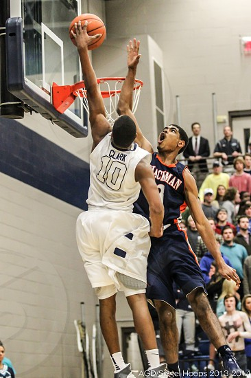 Basketball game; player dunking over an attempt to block. photo