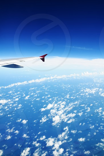 Wing of an airplane against blue sky horizon. photo