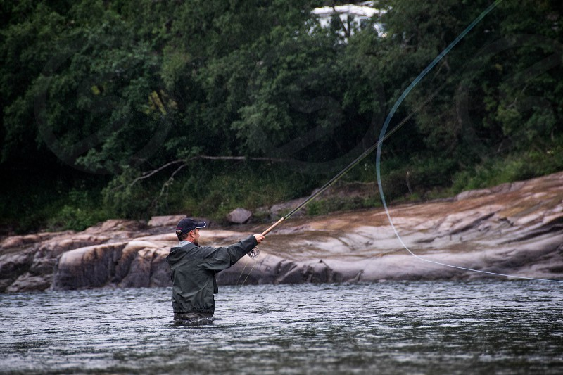 A fisherman throwing his fly fishing line fishing for salmon and trout. photo