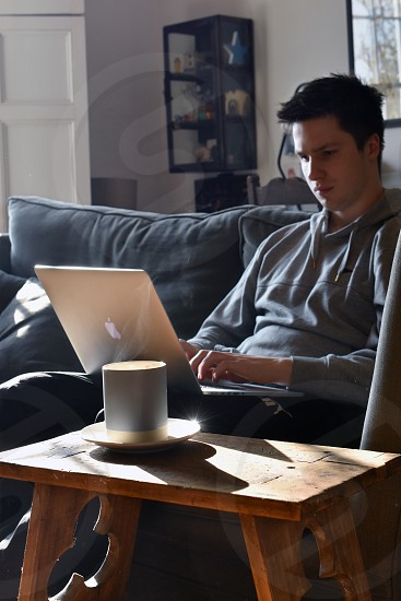 Young man relaxing on sofa using laptop computer. photo