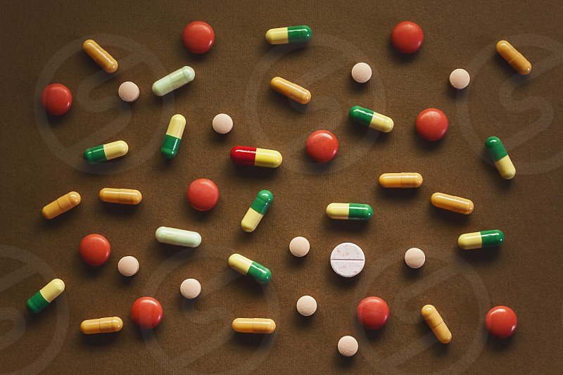 Various pills and tablets on brown textured background. Abstract composition.  photo