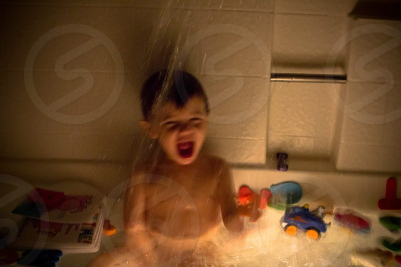 boy in bathtub with toys photo