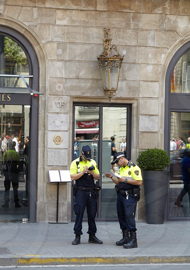 BARCELONA MAY 26: Two policemen communicate with each other near the la Rambla pedestrian area on May 26 2012 in Barcelona Spain. photo