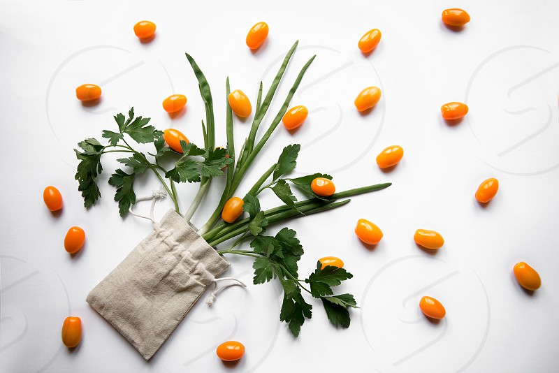 Beautiful flat lay of woven bag with orange color cherry tomatoes isolated on white background photo