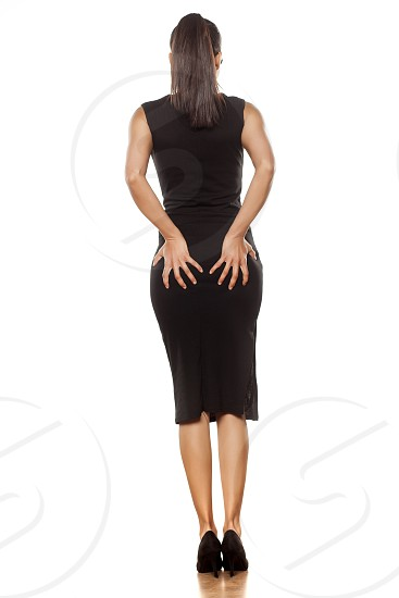 Back view of a young woman in a tight black dress holding her buttocks photo