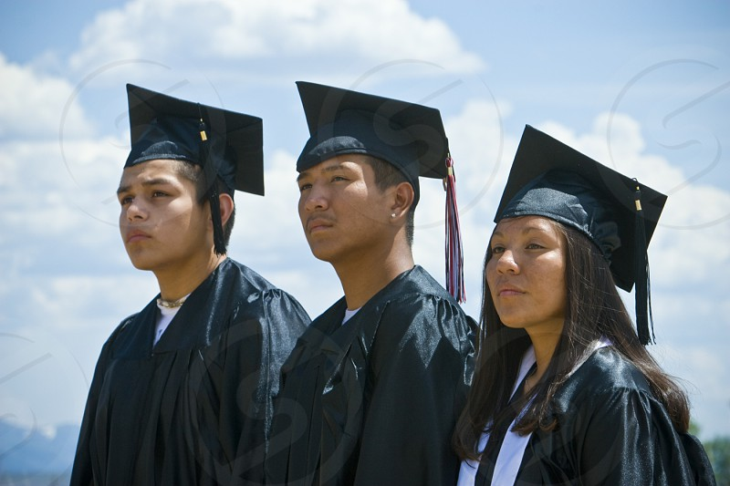 Three Native American students dressed in caps and gowns seriously look towards their future during  graduation ceremonies on the Fort Hall Indian Reservation Idaho photo