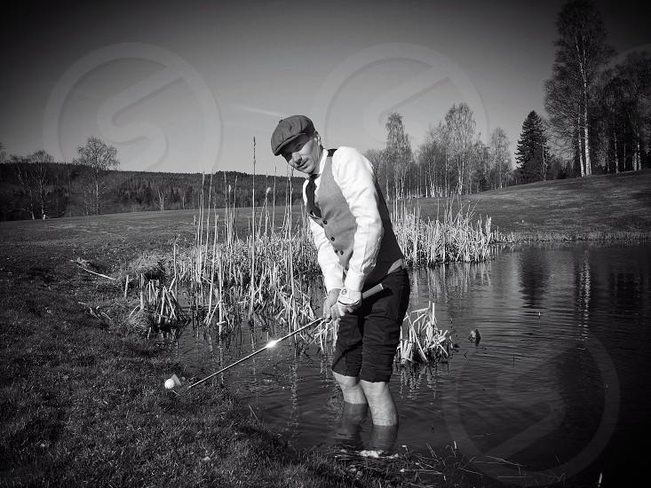 Water pond aiming old fashion club golf ball photo