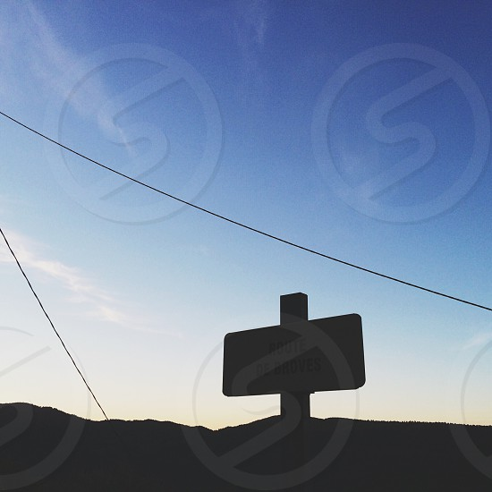 Blue sky behind dark road sign photo