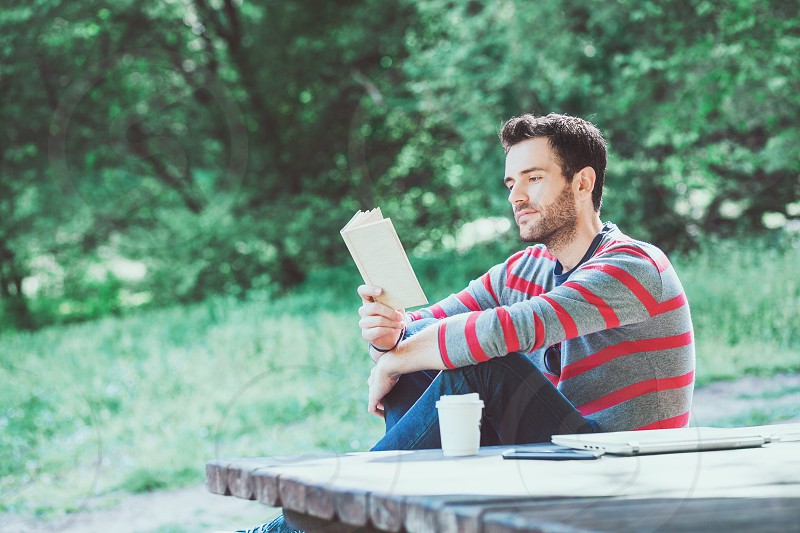 Young man reading a book in the park photo
