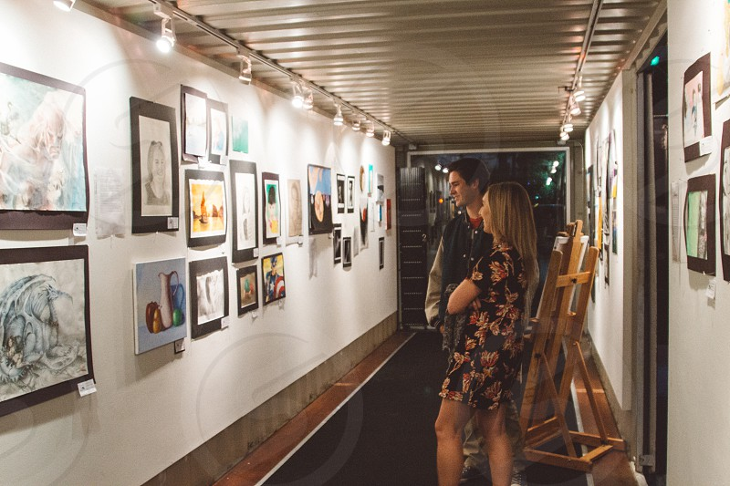 people looking at artwork on the wall photo