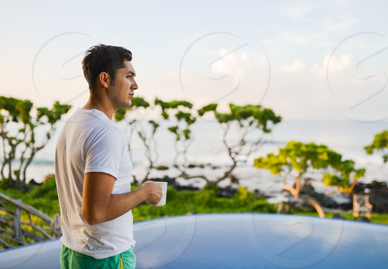 20-something man drinking coffee poolside in hawaii photo
