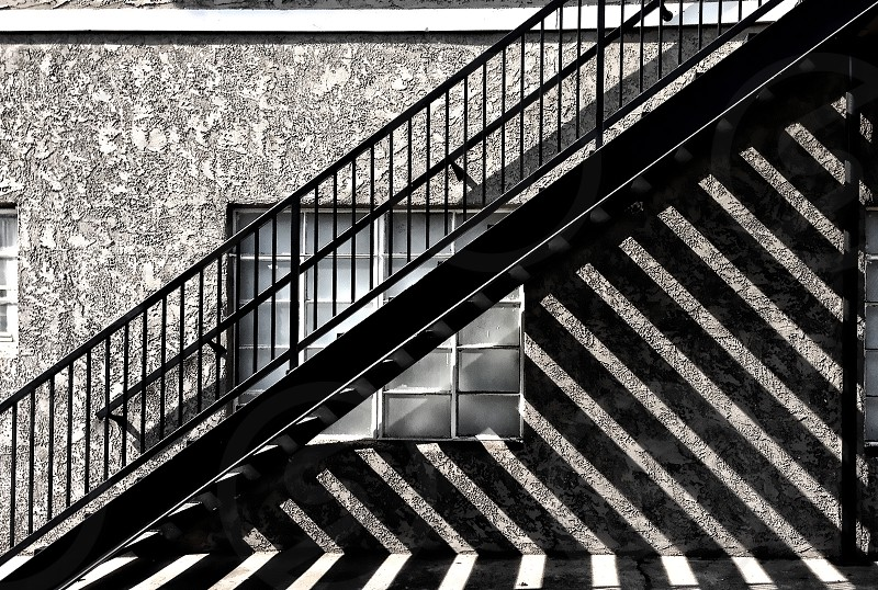 Sunlight through the steps on an outdoor staircase forms a dark and light striped pattern on the wall. photo