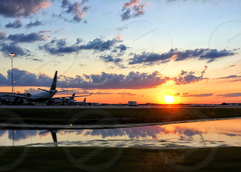 Sunset clouds reflection airport pond airplane photo