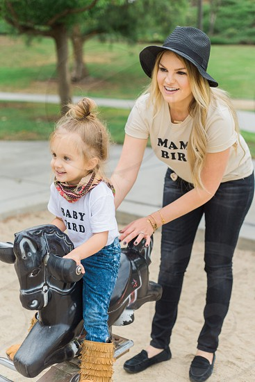 woman in brown printed crew neck shirt and black pants and shoes with black fedora hat assisting girl in white printed crew neck shirt blue denim pants riding black rocking horse photo