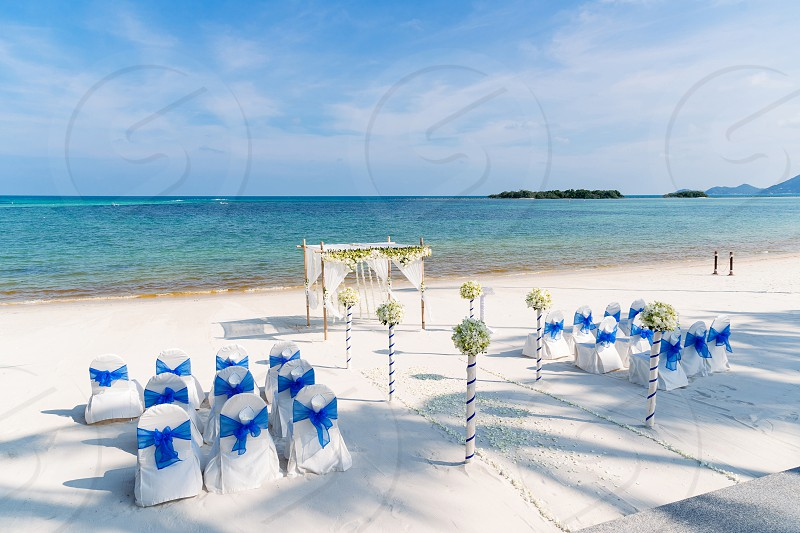 Beach wedding setting white cover chairs with blue organza Flower decoration on the aisle way and arch. Sea view background. photo