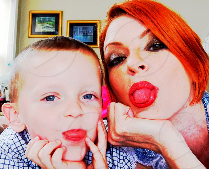 woman and boy sticking out tongues photo