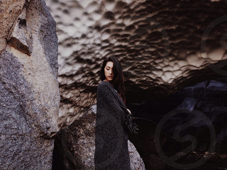 woman in black cloak standing near the cave photo
