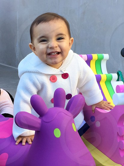 Baby girl standing between her toys smiling happily at the camera. photo
