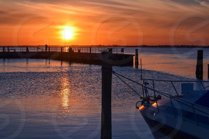 white motor boat dock on post near body of water photo