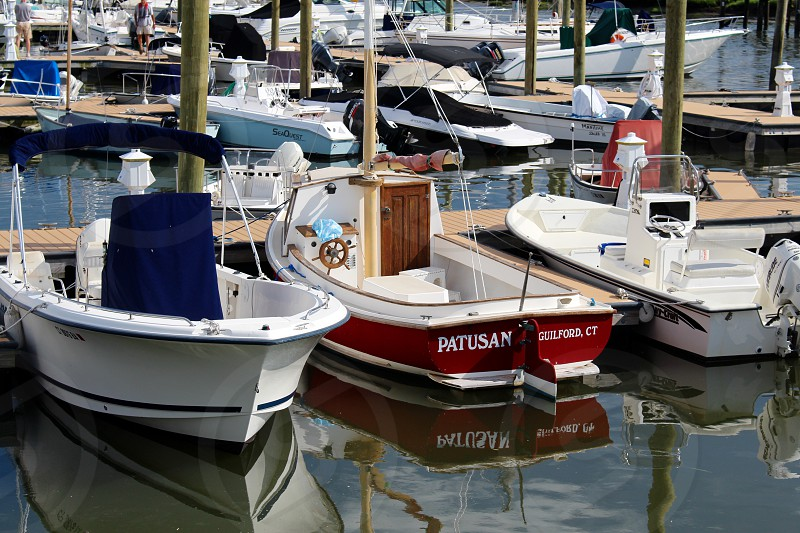white red blue boats with outboard motors at dock during daytime photo