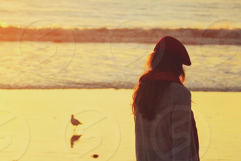 woman walking on beach wearing red cap photo