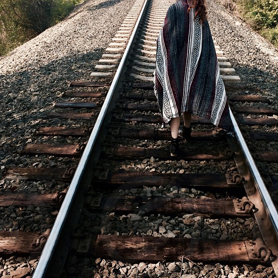woman wearing black gray white and red Greek key printed dress standing on train track photo