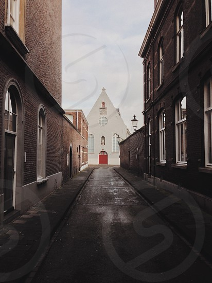 alleyway towards white church with red arch door under white and blue sunny cloudy sky photo