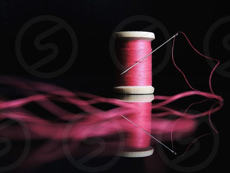 pink tread spool with needle photo