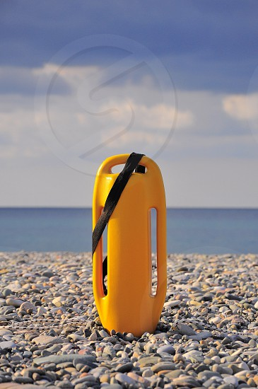 sea and stones with yellow plastic device photography photo