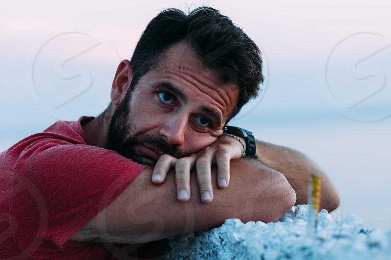 Young sad man by the sea looking at horizon photo