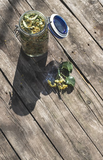 Jar with Linden blossom on wooden table. Sunny day photo