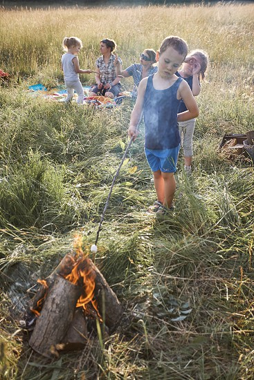 Little boy roasting marshmallow over a campfire. Family spending time together on a meadow close to nature. Parents and children sitting on a blanket on grass. Candid people real moments authentic situations photo
