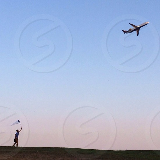 man with net catching plane photo