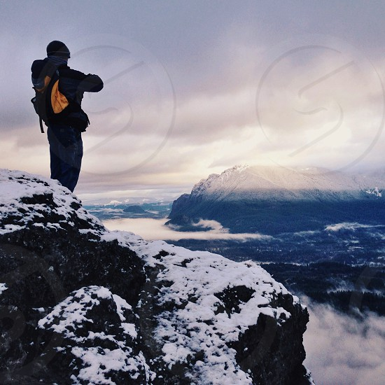 man standing on a snow cliff photo