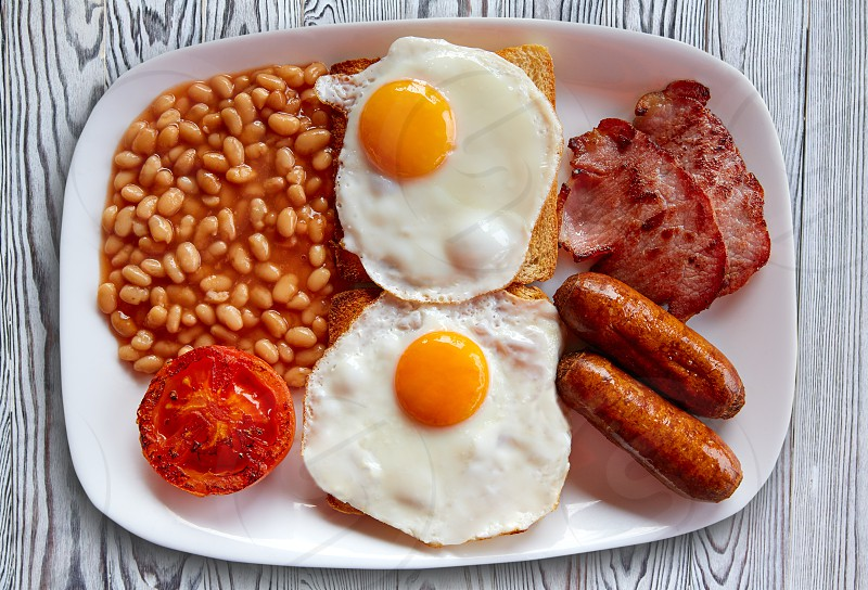 English breakfast with two eggs sausage beans bacon and grilled tomato photo