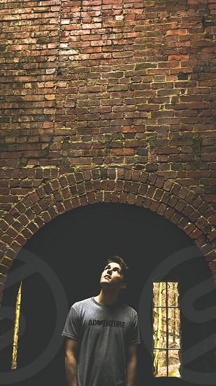 man under a concrete brick arch photo