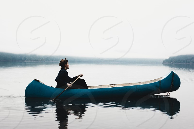 woman in black in blue canoe in middle of calm lake photo