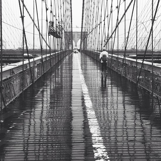 man walking in a bridge grayscale photo photo