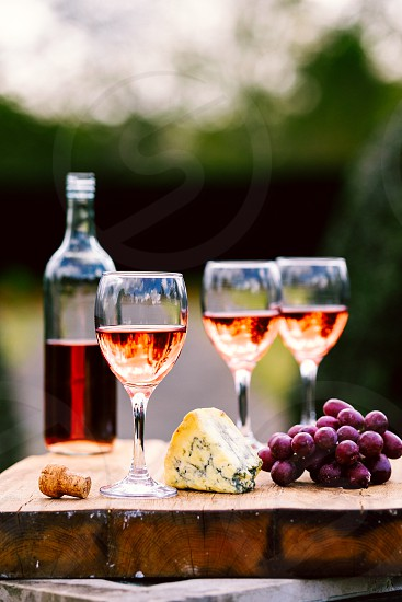 Rose wine filled bottleglasses and a cork on a large cheese board with grapes and stilton cheese in a natural light environment with a garden background photo