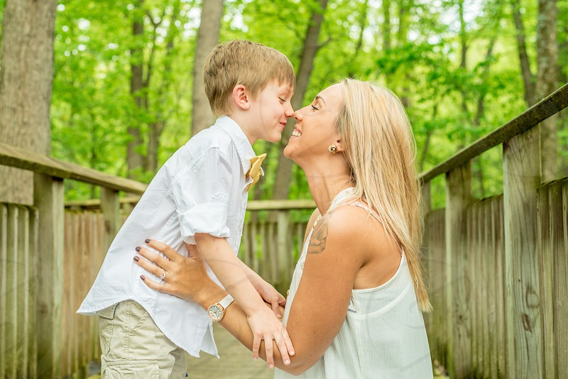 close up photography of a woman holding boy in a tree house photo