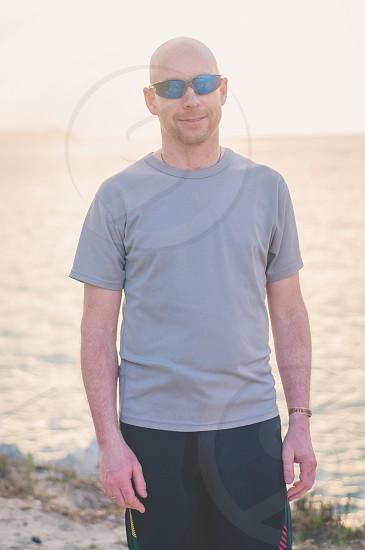 man wearing gray crew neck shirt and black shorts photo