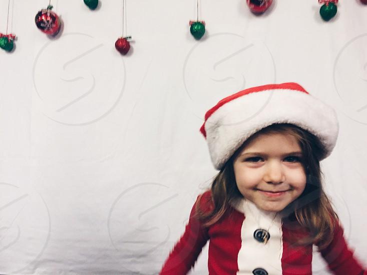 Little girl in Santa pajamas and Santa hat  photo