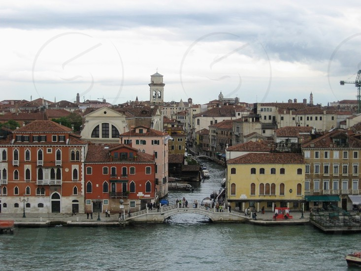 venice italy from the water  traditional historic cityscape showing  section of venice with traditional terracotta and ochre painted houses churches and people walking over a bridge by the canal photo