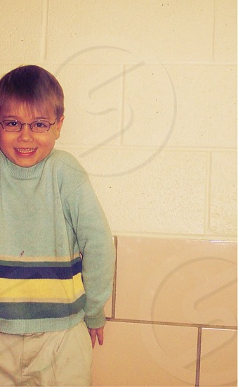 boy in grey blue and yellow striped sweater with black rimmed eyeglasses photo